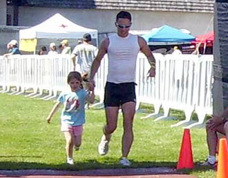 dad young daughter finishing triathlon