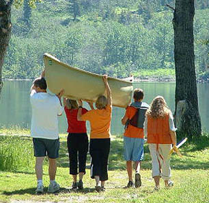 family-carrying-boat-to-lake