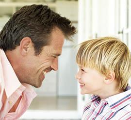 dad school-age son smiles face-to-face