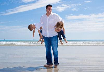 dad-carrying-2-preschool-kids-beach-laughing