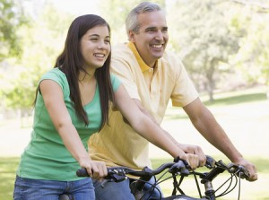dad-teen-daughter-riding-bikes-smiling-300x223
