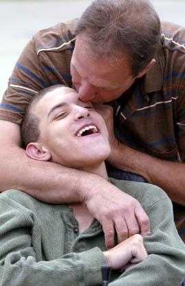 dad-teen-special-needs-son-hug-forehead-kiss