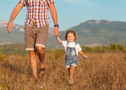 Father and daughter walking on the field