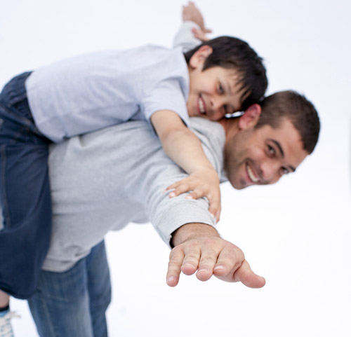 dad-school-age-son-on-back-airplane