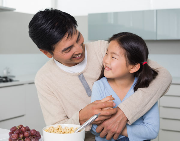 Cheerful father with young daughter having cereals in the kitchen at home