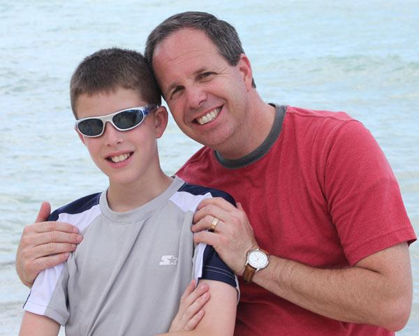 dad-teen-son-side-hug-on-water