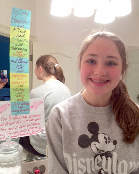 Here's Brittney sitting next to the messages that her dad, Dan, left on her bathroom mirror. He regularly writes to her now and reports that she never takes them down.