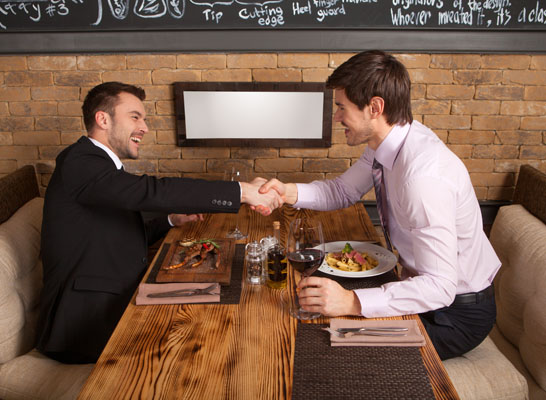 men laugh together while sitting in cafe. two man holding hands