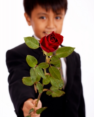 school-age boy presenting rose