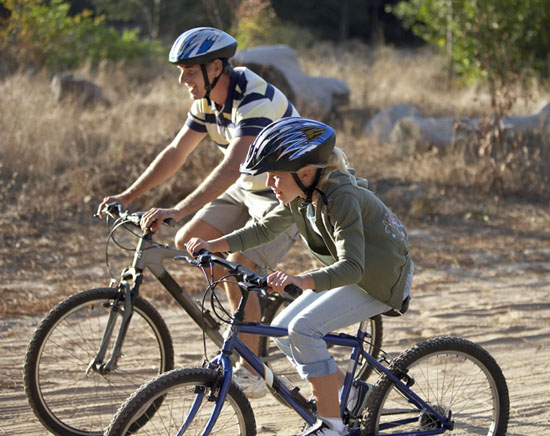 Father and daughter (8-10) cycling on dirt track in countryside,