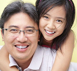 asian-dad-school-age-daughter-hug-over-shoulder-smiles