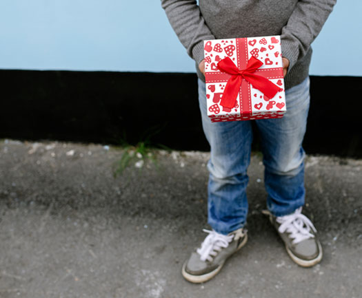 child holding Christmas gift waist down