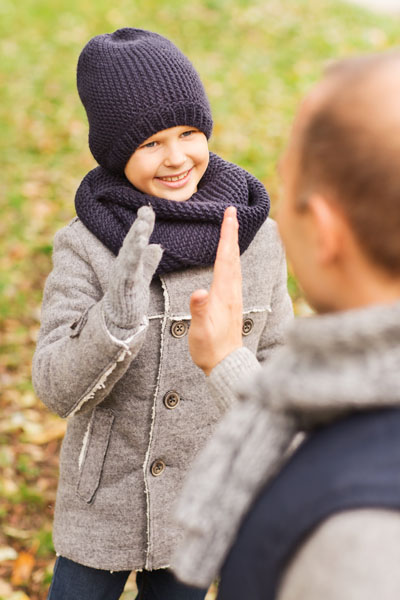 happy father and son making high five in park