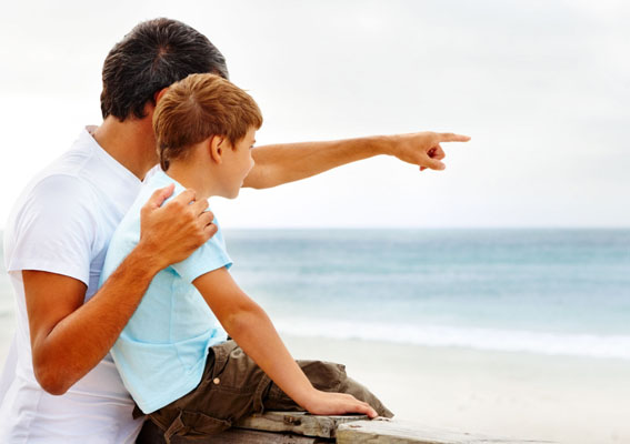C4P591 Father and son on a beach vacation together, father pointing towards the sea